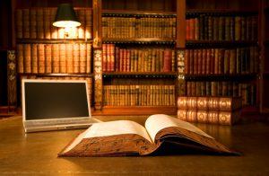 Computer portatile in libreria classica con libri in serie di sfondo